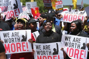 OAK BROOK, IL - MAY 21:  Fast food workers and activists demonstrate outside the McDonald's corporate campus on May 21, 2014 in Oak Brook, Illinois. The demonstrators were calling on McDonald's to pay a minimum wage of $15-per-hour and offer better working conditions for their employees. Several protestors were arrested after they entered and ignored police orders to leave the McDonald's campus.  McDonald's is scheduled to hold its annual shareholder's meeting tomorrow at the campus.  (Photo by Scott Olson/Getty Images)
