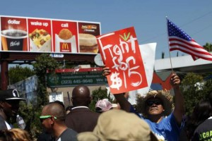 Fast-food workers and supporters organized by the Service Employees International Union (SEIU) protest in front of a McDonald's Corp. billboard on the street in Los Angeles, California, U.S., on Thursday, Aug. 29, 2013. Fast-food workers in 50 U.S. cities plan to walk off the job today, ratcheting up pressure on the industry to raise wages and demanding the right to wages of $15 an hour, more than double the federal minimum of $7.25. Photographer: Patrick T. Fallon/Bloomberg via Getty Images