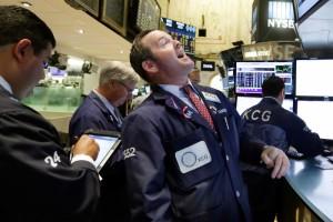 Specialist Charles Boeddinghaus, center, works on the floor of the New York Stock Exchange Thursday, Aug. 27, 2015.
