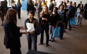 Jobseekers wait to talk to a recruiter (L) at the Colorado Hospital Association's health care career event in Denver October 13, 2014.