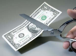 Dollar bill being cut with scissors